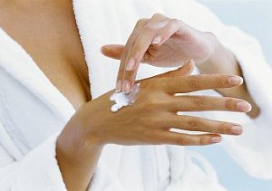 Woman in a white bathrobe applying moisturizer to her hand
