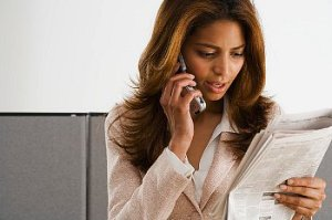 Business woman talks on the phone while looking at paperwork
