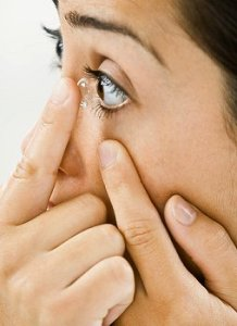 Woman putting contact in her eye