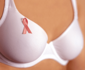 A white bra with a breast cancer ribbon pinned on it