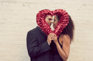 A couple holding a shiny streamer heart