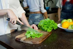 hand of a woman housewife preparing dinner, lettuce on a cutting board