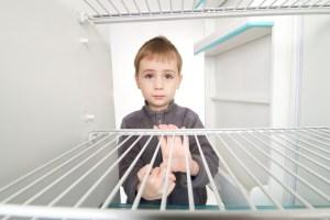Boy looking into empty refrigerator.