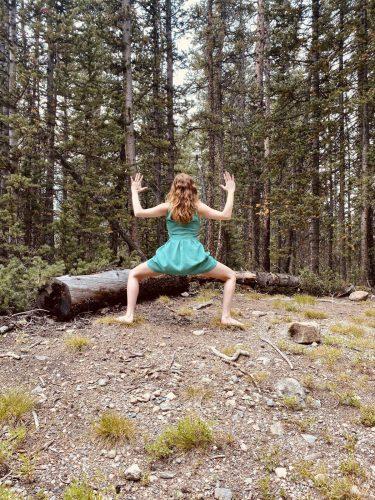 Utkata Konasana - standing goddess pose - yoga pose forest yogi girl wearing green dress, outdoors barefoot yoga in the woods