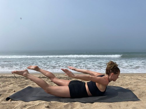 Salabhasana - locust pose - yoga pose girl sunny day yoga on the beach
