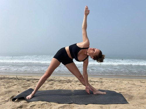 Trikonasana - triangle pose - yoga pose girl sunny day yoga on the beach