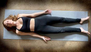 shavasana savasana - corpse pose - yoga pose girl red hair wearing black on gray yoga mat