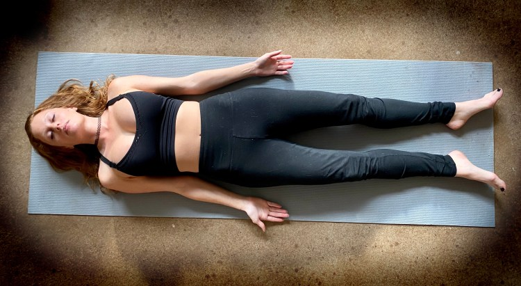 shavasana savasana - corpse pose - yoga pose girl red hair wearing black on gray yoga mat