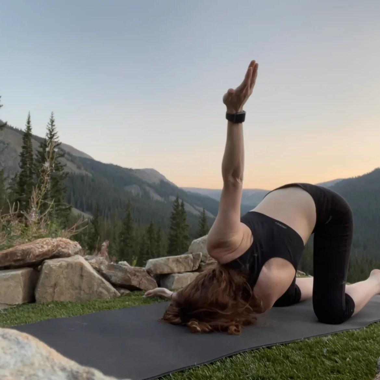 Parsva Balasana - Thread the Needle Pose - yoga pose yoga girl wearing black doing yoga outside in the rocky mountains