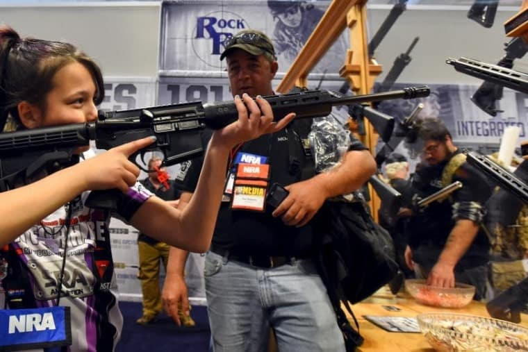 A girl tests rifles at a trade booth during the National Rifle Association's annual meeting in Nashville, Tennessee, this year. Photo by Reuters.