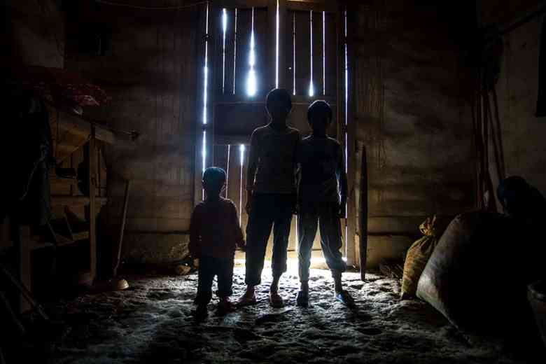 The Huang children stand in the light of the doorway. Their home is not typically lit by electric light so much of it remains dark when the doors are closed, even in the middle of the day.
