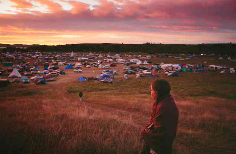 Susan Leopold of the Patawomeck Tribe of Virginia, watches the sun rise over an encampment where thousands have come to protest an oil pipeline, they thread through an arcade of flags whipping in the North Dakota wind. Each represent one of 280 Native American tribes that have flocked here in what activists are calling the largest, most diverse tribal action in at least a century, perhaps since Little Bighorn.