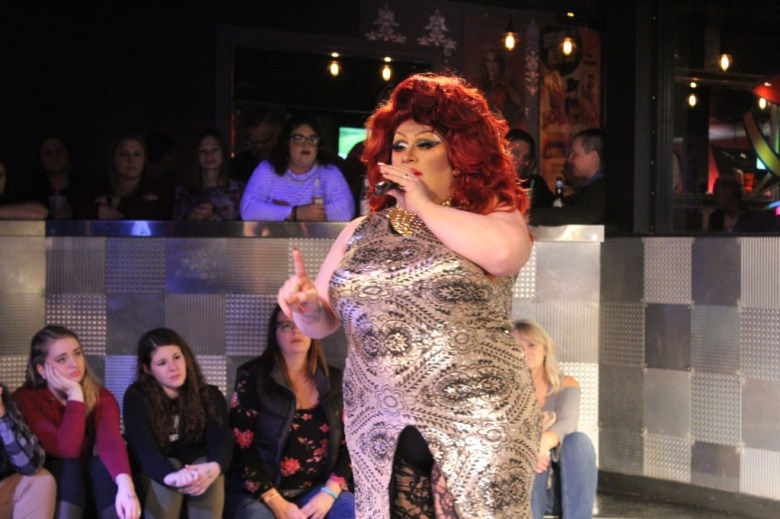 Drag queen with bright red hair and a shiny dress performs before a crowd of spectators