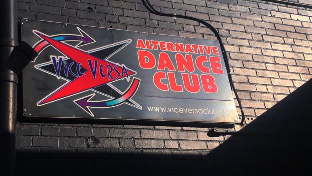 A sign on a brick wall advertises a bar