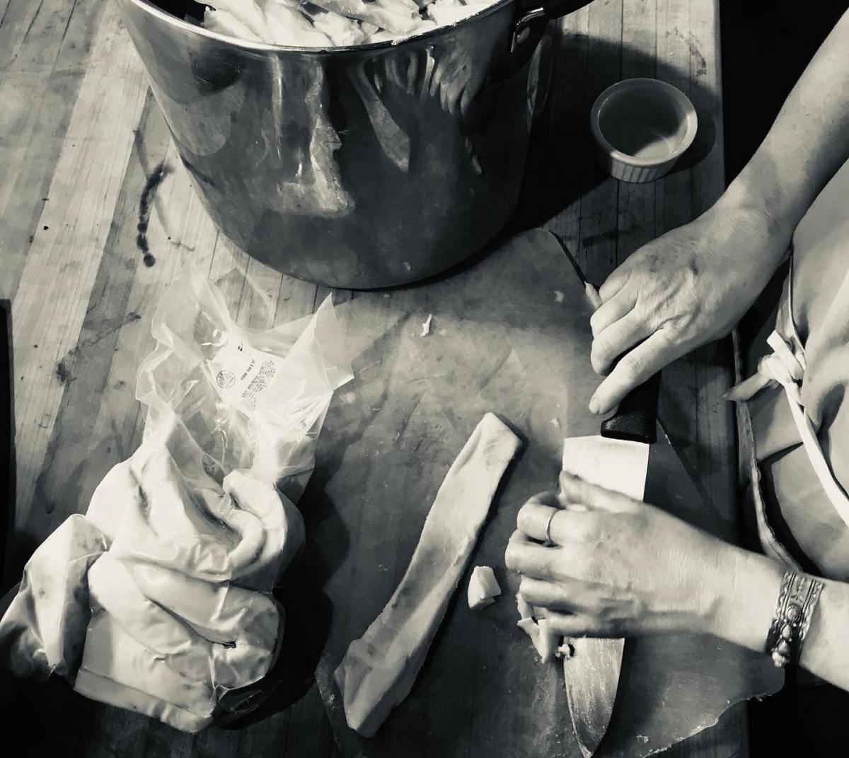 Black and white photo of Shannon Hayes' hands chopping and rendering lard.
