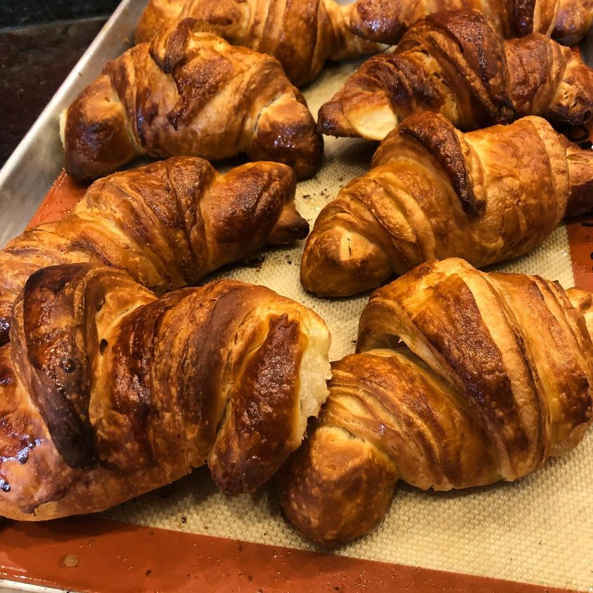 Two rows of golden-brown croissants sitting on a pan.