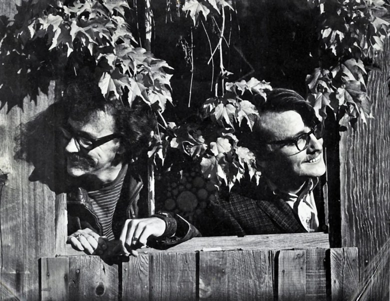 Black and white photo of Gurney Norman and Ed McClanahan peering over a fence side by side.