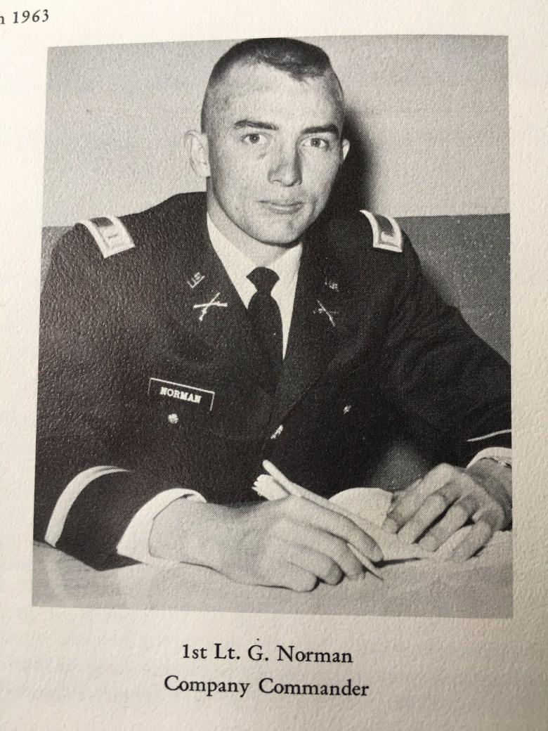 Black and white photo of Gurney Norman sitting at a table in military dress.