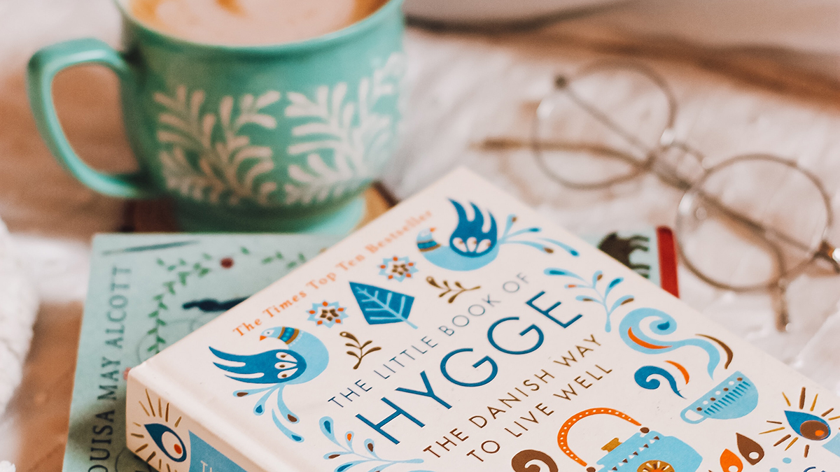 Photo of hygge book on a table with coffee mug and glasses