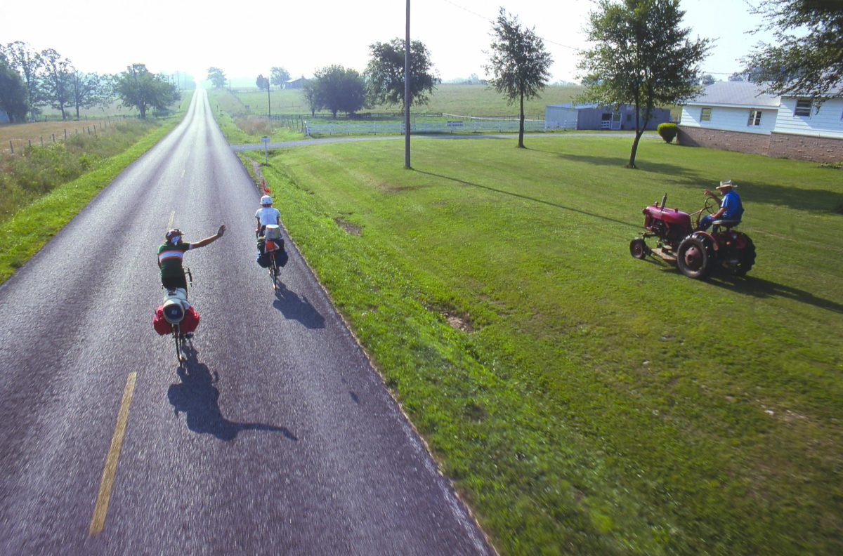 Two bikers on a paved trail wave to a man riding a tractor in his front yard