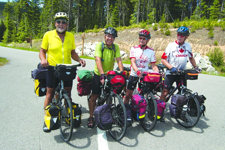 Four male bikers stop for a photo break while on the crossroads of a paved bike trail