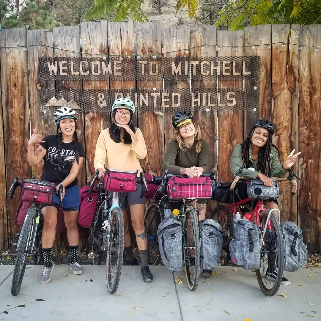 Four bikers pose for a photo in front of a welcome sign for Michell, Oregon and the Painted Hills