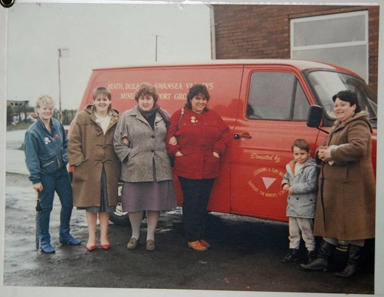 Five women and one child stand in front of the LGSM van.