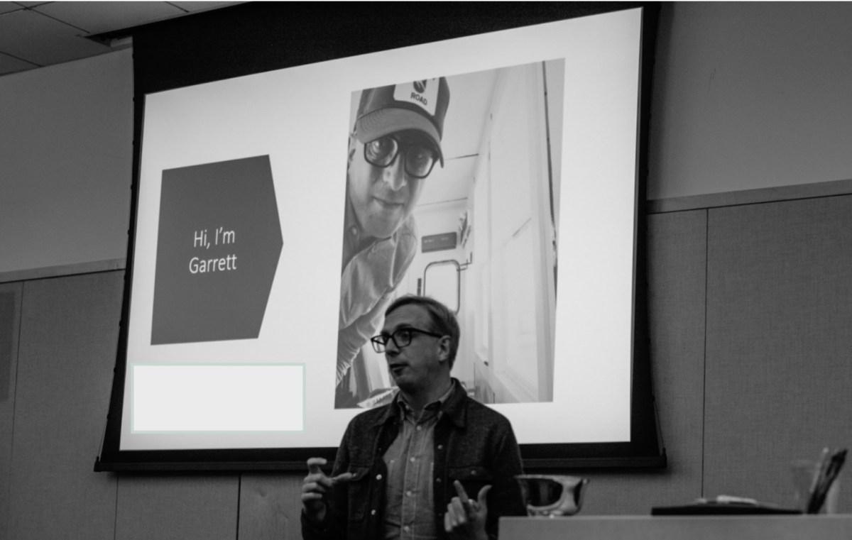 "Black and white photo of Garrett Bucks speaking with a screen projected behind him that reads ""Hi, I'm Garrett."""