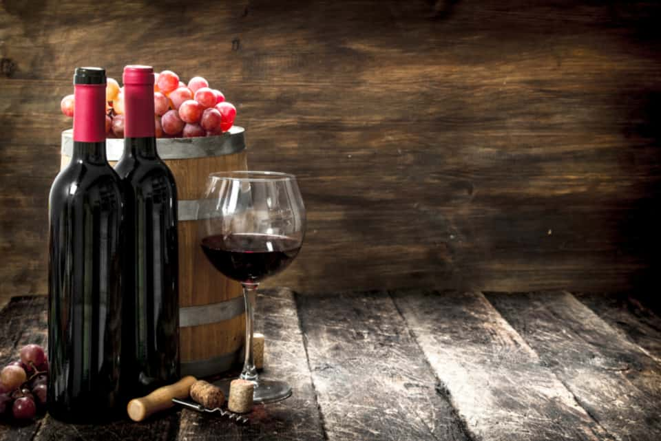117   A barrel with red wine and freshly grapes. On a wooden background.