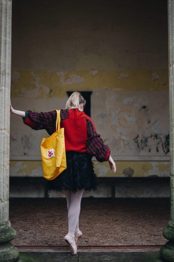 Back view of red upcycled acrylic wool jumper with tartan sleeves with green jersey and black tutu with textured details and yellow tote bag with Daines atelier label branding posing at the Sydney gardens.
