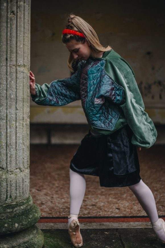 Green silk quilted batwing jumper made with an upcycled silk panel and green velvet. Orange zerowaste headband and long black shiny boxing shorts.