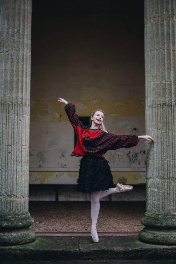 Red acrylic jumper with tartan worn by ballerina posing at the Sydney gardens
