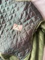 Detail shot of front of green batwing with velvet and vintage quilted silk panel featuring it's original label