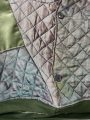 Detail shot of green upcycled batwing featuring upcycled quilted silk vintage jacket with button and green velvet