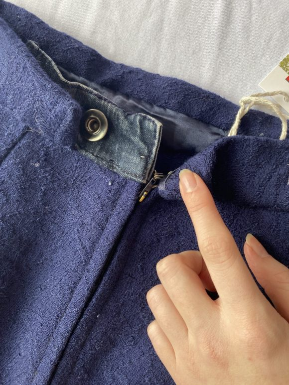 Detail shot of back fastening zip button and hook and eye made from vintage skirt and upcycled denim.