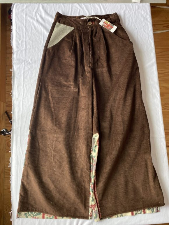 Flatlay front wide leg brown corduroy trousers with irregular wool pocket and pleating in waistbanf