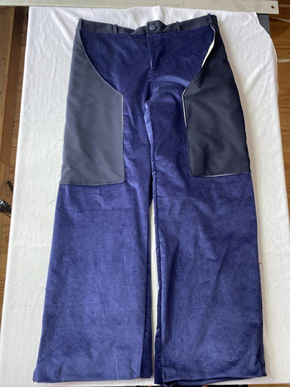 Front flatlay of blue corduroy straight leg trousers with long wool pockets and fly fastening made from dead stock corduroy.