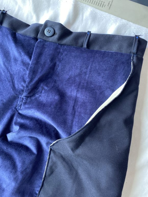 Detail shot of top front of blue corduroy trousers with wooden button and long wool pocket with top stitching.