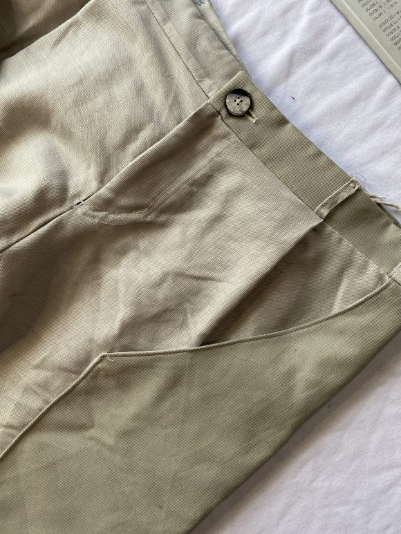 Detail shot of wooden button on front of off white made to measure trousers. Showcasing button loops and top stitching