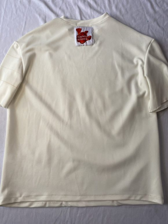 Flat lay back of oversized white tee shirt in scuba jersey with Daines atelier cotton logo in Center neck