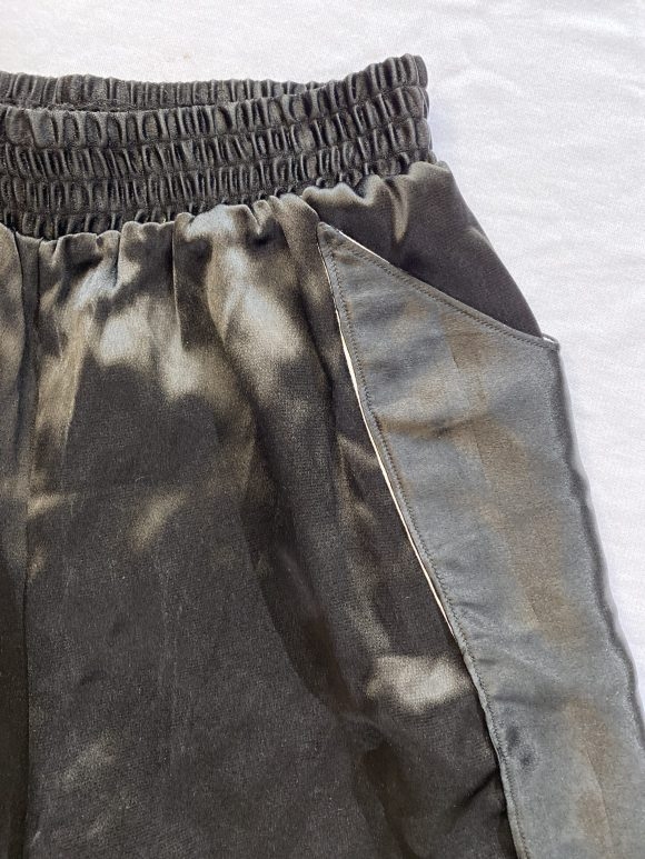 Detail shot of elasticated waistband on satin black boxing shorts with top stitching detail on long pocket