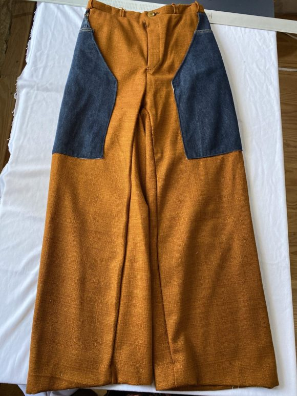 Flatlay of unisex high waisted trousers in orange wool with upcycled denim pockets