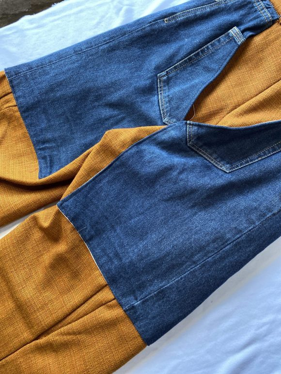 Back detail shot of denim pockets on trouser chaps made in orange wool. Can be made to measure and the fabric is dead stock and upcycled