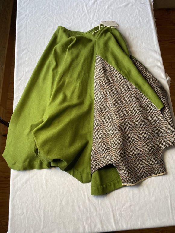 Green wool circular skirt flat lay showcasing tartan wool panel. Made from dead stock materials and zero waste