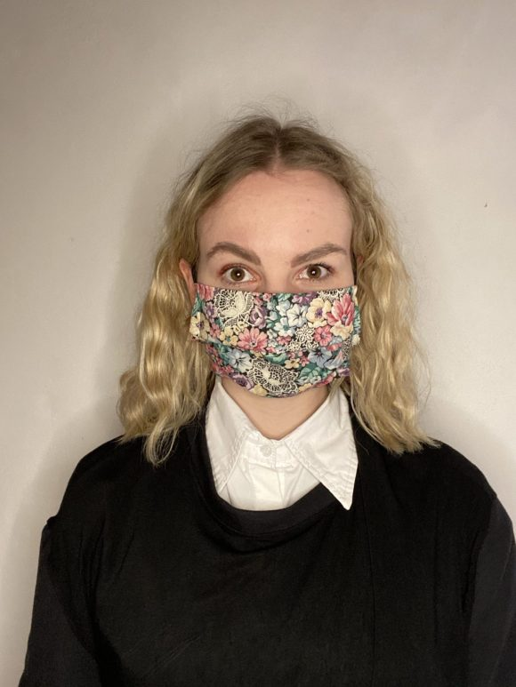 Handmade breathable facemask with filter pocket and adjustable elastic made from vintage remnant materials In black and pink floral