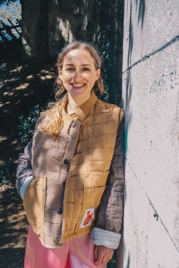 The brown quilted jacket is made from upcycled vintage remnants and features a boxy silhouette and unisex design. Photography by Maisie Lee Walker in Bath, Sydney Gardens