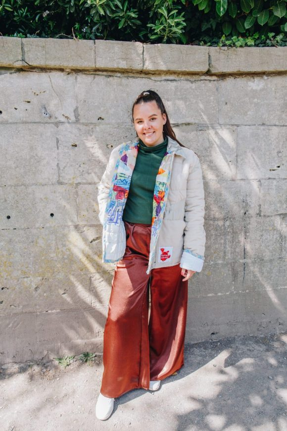 Rosie Sanders wears the beige quilted jacket made from upcycled materials. The lining is a multi colour link print. She also wears the green jersey turtleneck and brown mimosa Trousers. Photograph by Maisie Lee Walker in Bath.