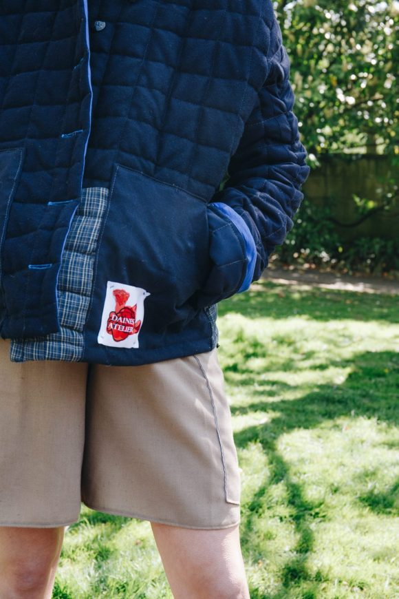Close up of the blue wool quilted jacket featuring Daines Atelier Cotton Logo. photography by Maisie Lee Walker in Bath