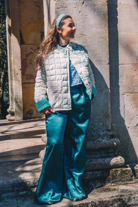 Martha Rice wears the Green One-of-a-kind Quilted Jacket with a Blair Waldorf Headband, floral best and green wide leg Mimosa Trousers. Photography by Maisie Lee Walker in Sydney Gardens, Bath