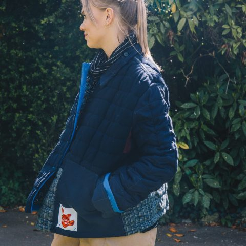 Sophie Wright wears the blue quilted jacket made from upcycled deadstock materials. Remnant wool jacket. Photography by Maisie Lee Walker in Bath Sydney Gardens